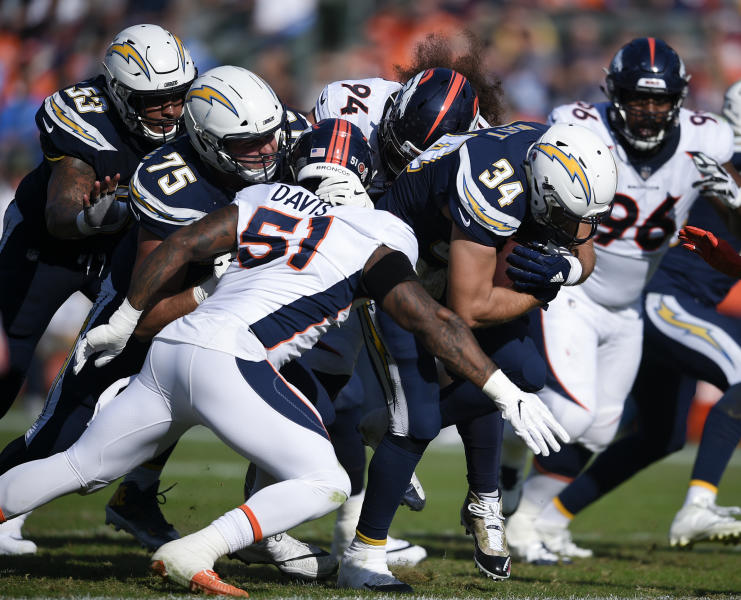 FILE - In this Sunday, Nov. 18, 2018, file photo, Los Angeles Chargers fullback Derek Watt, right, runs the ball while Denver Broncos nose tackle Domata Peko Sr., center, and linebacker Todd Davis defend during the first half of an NFL football game in Carson, Calif. Derek Watt and J.J. Watt have played against each other in the front and back yard of their parent's home in Waukesha, Wisconsin. There will be bigger stakes and bragging rights on the line on Sunday, Sept. 22, 2019 when the Los Angeles Chargers host the Houston Texans.(AP Photo/Kelvin Kuo, File)