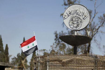A Syrian national flag flutters next to the Islamic State's slogan at a roundabout where executions were carried out by ISIS militants in the city of Palmyra, in Homs Governorate, Syria in this April 1, 2016 file photo. REUTERS/Omar Sanadiki/Files