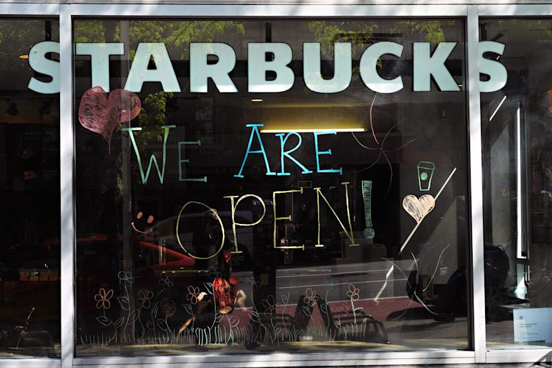 NEW YORK, NEW YORK - MAY 10: A window at Starbucks reads 'WE ARE OPEN!' during the coronavirus pandemic on May 10, 2020 in New York City. COVID-19 has spread to most countries around the world, claiming over 283,000 lives with over 4.1 million infections reported. (Photo by Cindy Ord/Getty Images)