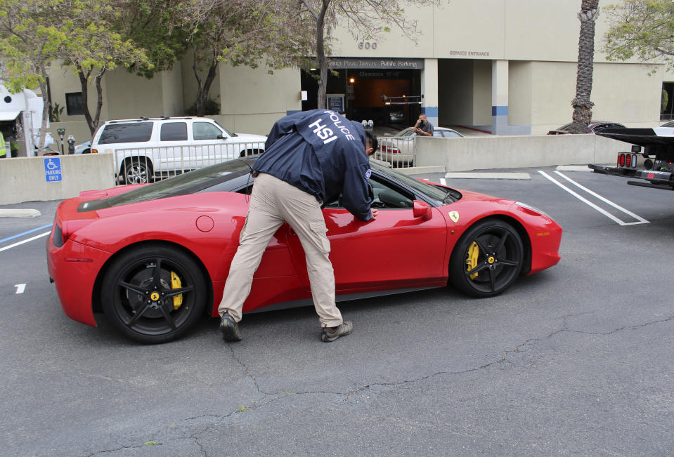 This photo provided by U.S. Immigration and Customs Enforcement shows a special agent with HSI Los Angeles's El Camino Real Financial Crimes Task Force seize a Ferrari from an Orange County businessman on Friday, April 7, 2021 Santa Ana, Calif. Mustafa Qadiri, 38, of Irvine, was named in a federal grand jury indictment and has pleaded not guilty to charges he obtained $5 million in federal coronavirus-relief loans for phony businesses and then used the money for lavish vacations and to buy a Ferrari, Bentley and Lamborghini, prosecutors said Monday, May 10. (U.S. Immigration and Customs Enforcement via AP)