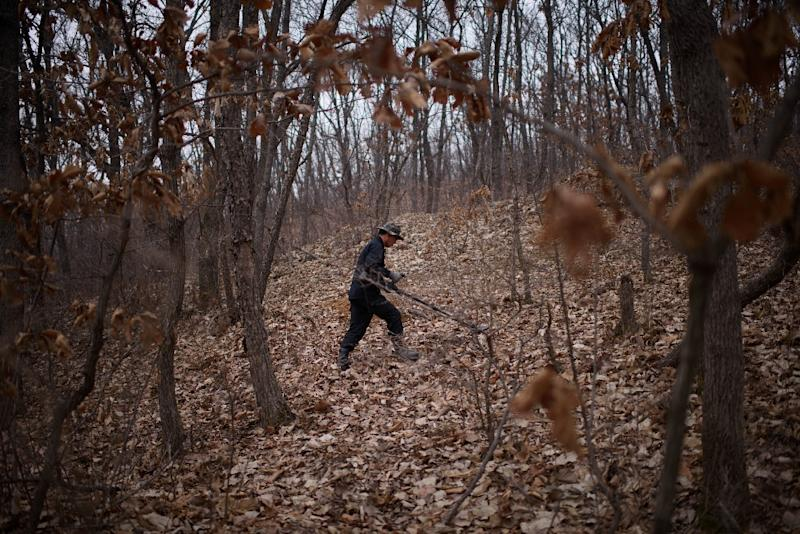 Kim Ki-Ho, head of the Korea Research Institute for Mine Clearance, hunts for landmines in woodland near the Demilitarized Zone in Yeoncheon, South Korea (AFP Photo/Ed Jones)