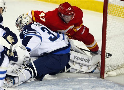Winnipeg Jets goalie Ondrej Pavelec, left, from the Czech Republic, collapses under the weight of Calgary Flames' Sven Baertschi, from Switzerland, during first-period NHL hockey game action in Calgary, Alberta, Friday, March 9, 2012. (AP Photo/The Canadian Press, Jeff McIntosh)