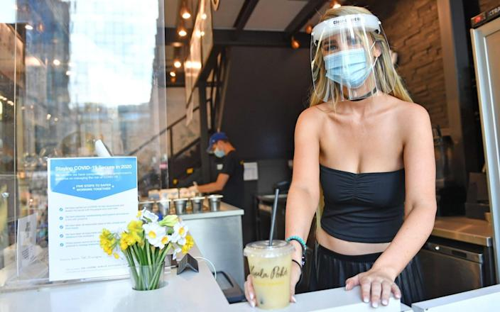 Felicity Whiston, wearing a face mask and guard, whilst serving drinks at take away restaurant Kuula Poke in Birmingham - Jacob King/PA