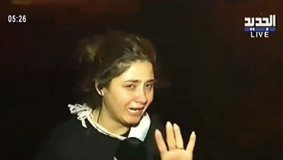 Pictured is Halima Tabiaa holding back tears as she reports live from the fires in Damour.