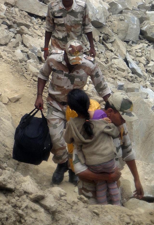 In this handout photograph received from the Indo Tibetan Border Police (ITBP) on June 25, 2013, members of the ITBP assist a young girl near Badrinath in northern Uttarakhand state. Indian officials stepped up efforts on June 25 to prevent an outbreak of disease in the northern Himalayan region devastated by landslides and flash floods, as rains hampered the rescue of thousands still stranded. AFP PHOTO/ITBP