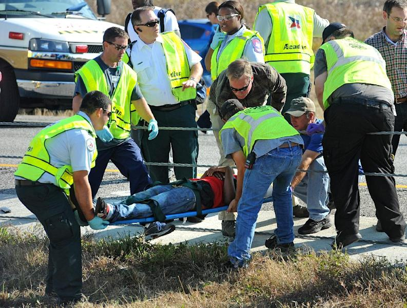 Emergency workers carry a victim across the Interstate 10 median after a massive auto accidentin Southeast Texas Thursday Nov. 22, 2012. The Texas Department of Public Safety says at least 35 people have been injured in a more than 50-vehicle pileup. (AP Photo/The Beaumont Enterprise, Guiseppe Barranco)MANDATORY CREDIT