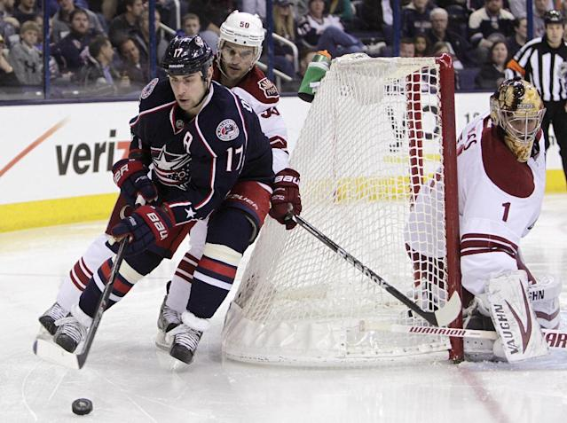 Columbus Blue Jackets' Brandon Dubinsky, left, carries the puck behind the net as Phoenix Coyotes' Antoine Vermette, center, defends and Thomas Greiss, of Germany, protects the net during the second period of an NHL hockey game Tuesday, April 8, 2014, in Columbus, Ohio. (AP Photo/Jay LaPrete)