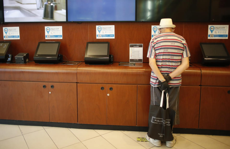 A man prepares to buy a ticket at a cinema after almost a year of theaters being closed due to the COVID-19 pandemic, in Buenos Aires, Argentina, Wednesday, March 3, 2021. (AP Photo/Natacha Pisarenko)