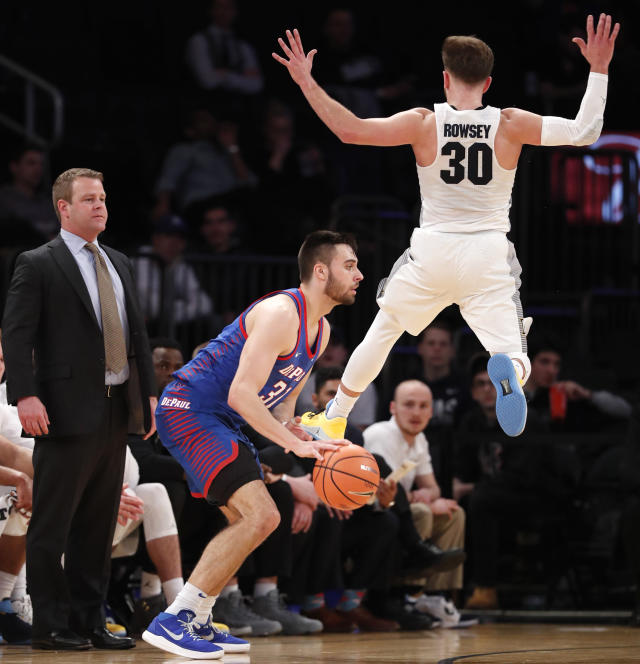 Marquette head coach Steve Wojciechowski, left, watches, as Marquette guard Andrew Rowsey (30) leaps in front of DePaul guard Max Strus (31) during the first half of an NCAA college basketball game in the first round of the Big East conference tournament, in New York, Wednesday, March, 7, 2018. (AP Photo/Kathy Willens)