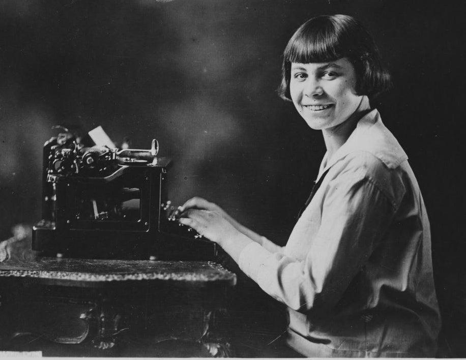 A teen in 1920 sits before a large typewriter