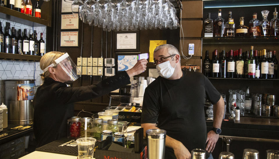 1920 Tavern Owner Jenna Aronowitz takes the temperature of bartender Shane Goode before the Roswell restaurant opens for sit down meals in Brookhaven, Ga., Monday, April 27, 2020. (Steve Schaefer/Atlanta Journal-Constitution via AP)