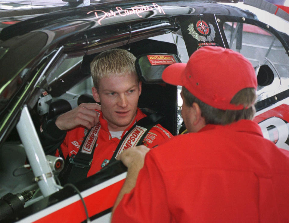 FILE - In this May 5, 1999, file photo, Dale Earnhardt, Jr., of Kannapolis, N.C., left, listens to a crew member as he sits in his Winston Cup race car before a practice session at Lowe's Motor Speedway in Concord, N.C. There's a pointed episode in Dale Earnhardt Jr.'s television show that encapsulates Earnhardt's remarkable transformation from a bashful third-generation racer into a multimedia personality. (AP Photo/Chuck Burton, File)