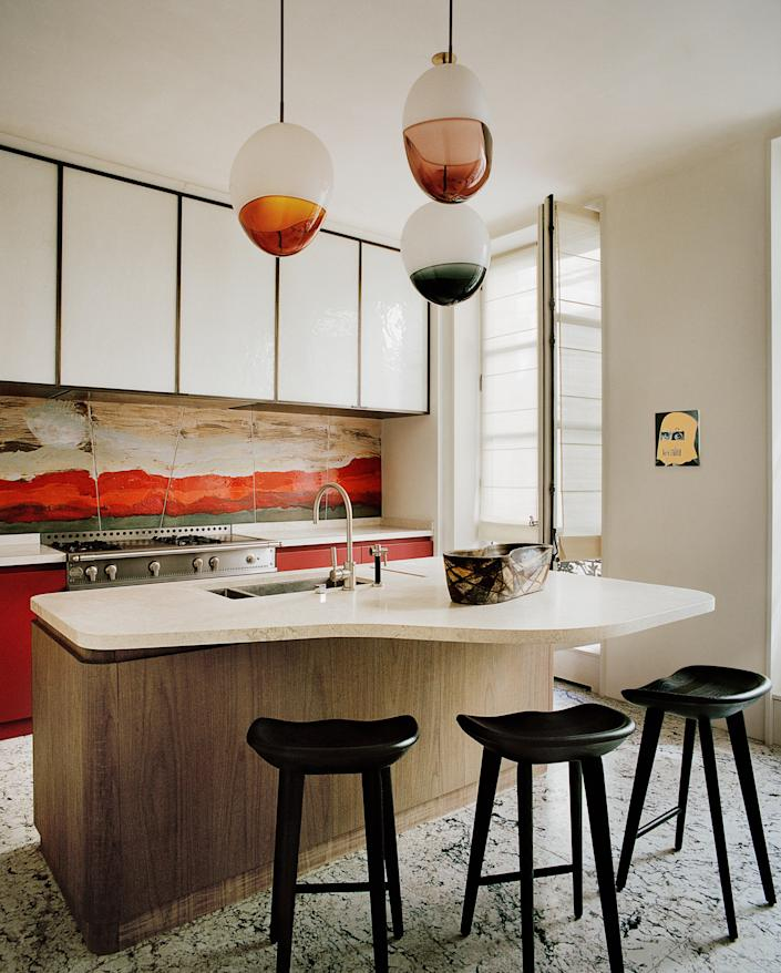 Sinuous silhouettes, crimson accents, and a dynamic mix of materials dazzle in the kitchen. Shown is a Paris project by Pierre Yovanovitch.