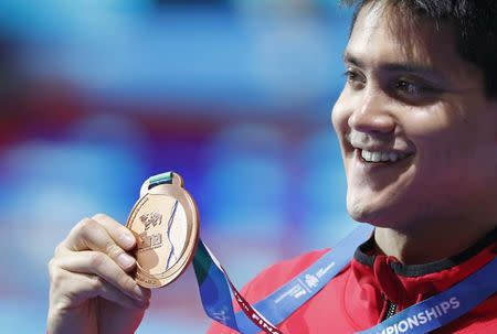 FILE PHOTO: Swimming – 17th FINA World Aquatics Championships – Men's 100m Butterfly awarding ceremony – Budapest, Hungary – July 29, 2017 – Joseph Schooling (bronze) of Singapore poses with the medal. REUTERS/Bernadett Szabo