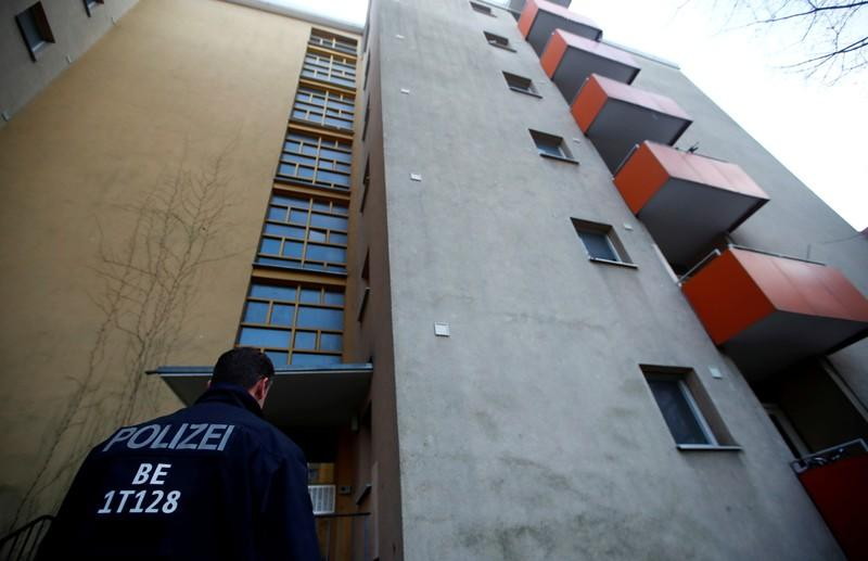 A police officer is seen outside the house of a Syrian man suspected of exchanging bomb building material that was arrested earlier today in Berlin