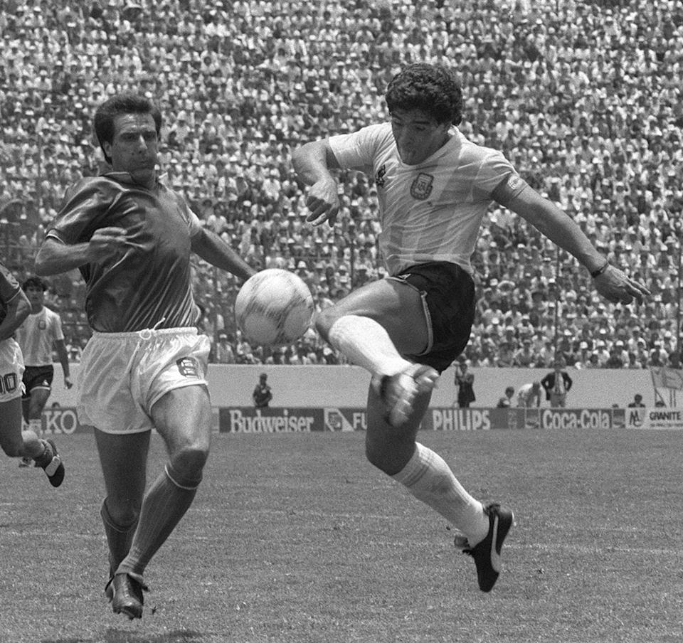 Argentinian forward Diego Maradona (R) kicks the ball past Italian defender Gaetano Scirea to tie the score at 1 during the World Cup first round soccer match between Argentina and Italy 05 June 1986 in Puebla. Argentina and Italy played to a 1-1 tie. AFP PHOTO/DANI YAKO (Photo credit should read STAFF/AFP via Getty Images)