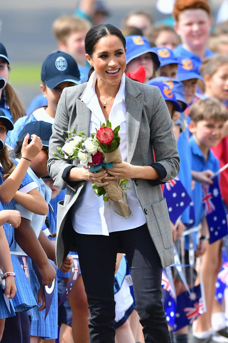 Meghan with a bunch of beautiful flowers given to her upon arrival in Dubbo. Photo: Getty, meghan markle prince harry dubbo, meghan markle prince harry australia, meghan markle serena williams jacket, meghan markle pregnant