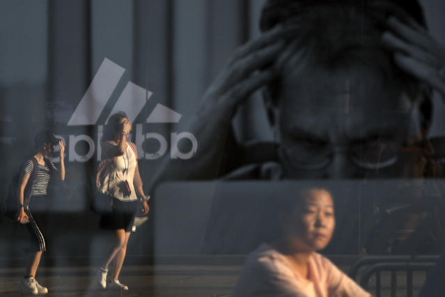 """<p>Women are reflected on an advertisement for Apple's MacBook computer on display near a shopping mall in Beijing, Thursday, September 6, 2018. China's government says it is ready to retaliate if U.S. President Donald Trump goes ahead with plans for another tariff hike on Chinese goods. The Commerce Ministry expressed confidence it can maintain """"steady and healthy"""" economic growth despite their spiraling trade battle. (AP Photo/Andy Wong) </p>"""