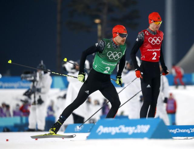 Nordic Combined Events - Pyeongchang 2018 Winter Olympics - Men's Team 4 x 5 km Final - Alpensia Cross-Country Skiing Centre - Pyeongchang, South Korea - February 22, 2018 - Vinzenz Geiger of Germany and Fabian Riessle of Germany exchange. REUTERS/Kai Pfaffenbach