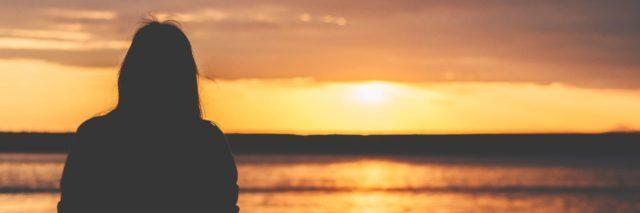 silhouette of a woman watching the sun set over the ocean