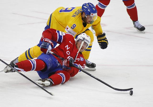 Norway's Anders Bastiansen, bottom, and Sweden's Niclas Andersen battle for the puck during the Group A preliminary round match at the Ice Hockey World Championship in Minsk, Belarus, Tuesday, May 13, 2014. (AP Photo/Sergei Grits)