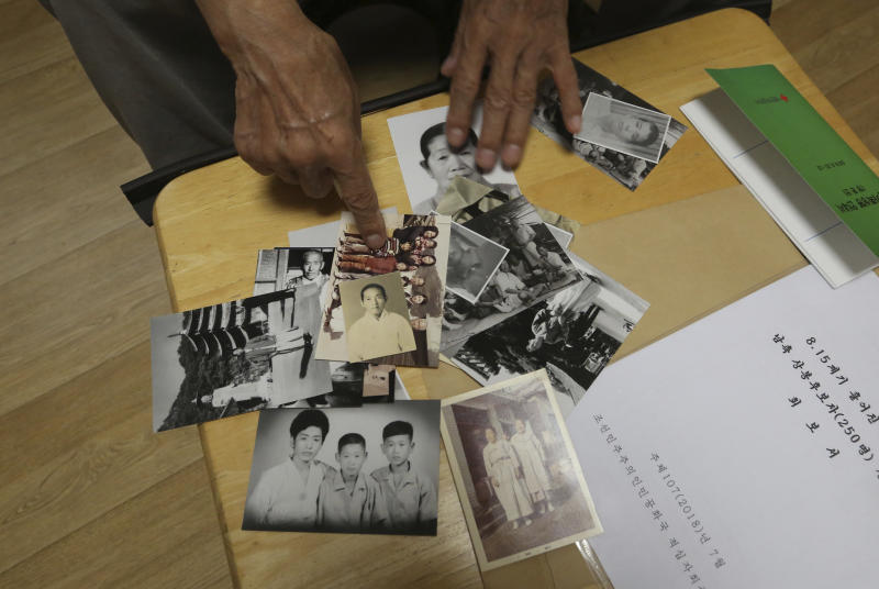 In this Aug. 17, 2018, photo, Lee Soo-nam, 76, explains about photos showing his family members during an interview at his home in Seoul, South Korea. Lee is among about 200 war-separated South Koreans and their family members who are crossing into North Korea for heart-wrenching meetings with relatives they haven't seen for decades. The week-long event beginning Monday at North Korea's Diamond Mountain resort come as the rival Koreas boost reconciliation efforts amid a diplomatic push to resolve the North Korean nuclear crisis.(AP Photo/Ahn Young-joon)