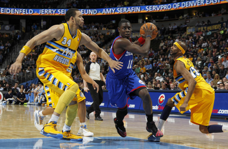 Philadelphia 76ers guard Jrue Holliday, center, drives the lane for a shot between Denver Nuggets forwards JaVale McGee, left, and Corey Brewer in the first quarter of an NBA basketball game in Denver, Thursday, March 21, 2013. (AP Photo/David Zalubowski)
