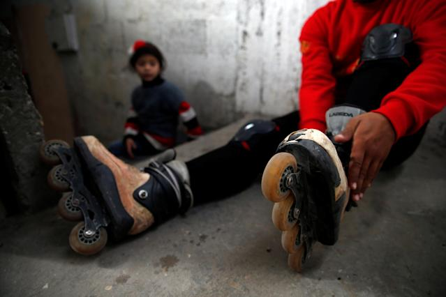 Palestinian Mustafa Sarhan, 19, a member of Gaza Skating Team, puts on his rollerblades in his family house in Gaza City March 18, 2019. Picture taken March 18, 2019. REUTERS/Mohammed Salem