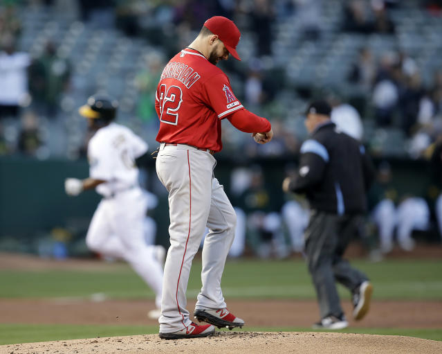 Los Angeles Angels pitcher Cam Bedrosian (32) waits for Oakland Athletics' Marcus Semien, left, to run the bases after hitting a home run in the first inning of a baseball game Tuesday, May 28, 2019, in Oakland, Calif. (AP Photo/Ben Margot)