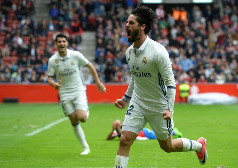 Real Madrid's Isco (R) celebrates after scoring a goal during their match against Real Sporting de Gijon at El Molinon stadium in Gijon on April 15, 2017