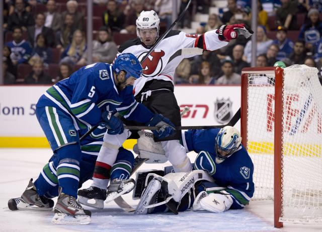 Vancouver Canucks defenseman Jason Garrison (5) tries to clear New Jersey Devils right wing Jaromir Jagr (68) from in front of Canucks goalie Roberto Luongo (1) during the first period of an NHL hockey game Tuesday, Oct. 8, 2013, in Vancouver, British Columbia. (AP Photo/The Canadian Press, Jonathan Hayward)