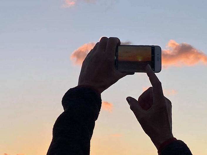 A woman aims for a photo of the sunset at Mallory Square on March 16, 2020.