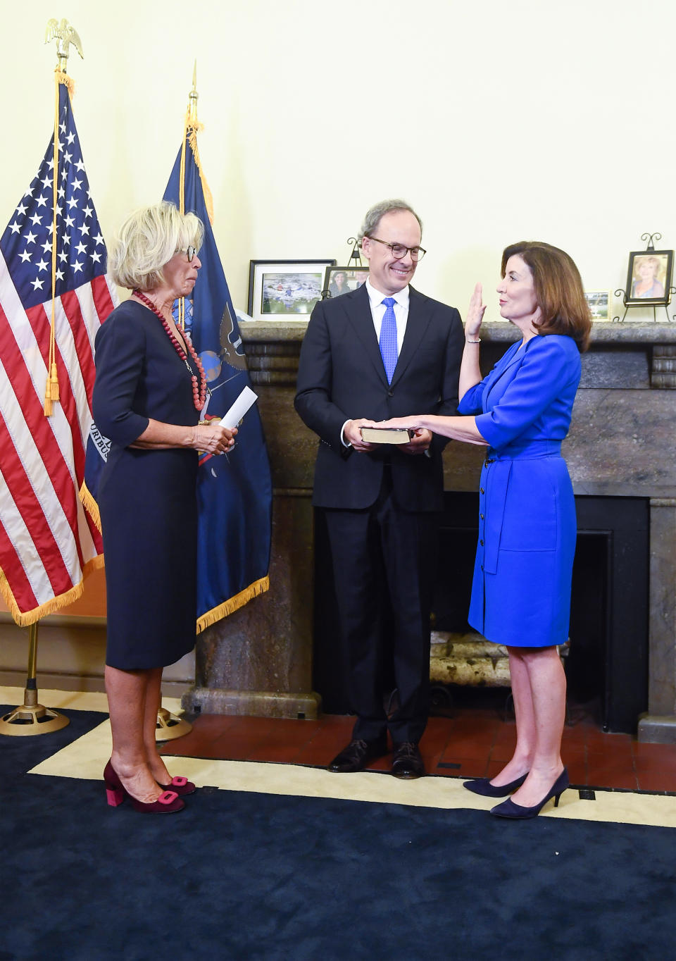 New York Chief Judge Janet DiFiore, left, swears in Kathy Hochul, right, as the first woman to be New York's governor while her husband Bill Hochul holds a bible during a swearing-in ceremony in the Red Room at the state Capitol, early Tuesday, Aug. 24, 2021, in Albany, N.Y. (AP Photo/Hans Pennink, Pool)