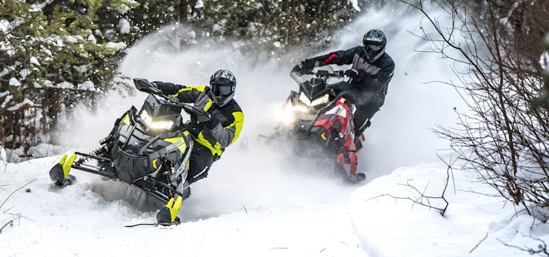 Snowmobiles racing through snow