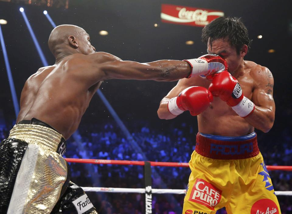 Floyd Mayweather, Jr. of the U.S. (L) lands a right against Manny Pacquiao of the Philippines in the sixth round during their welterweight WBO, WBC and WBA (Super) title fight in Las Vegas, Nevada, May 2, 2015. REUTERS/Steve Marcus