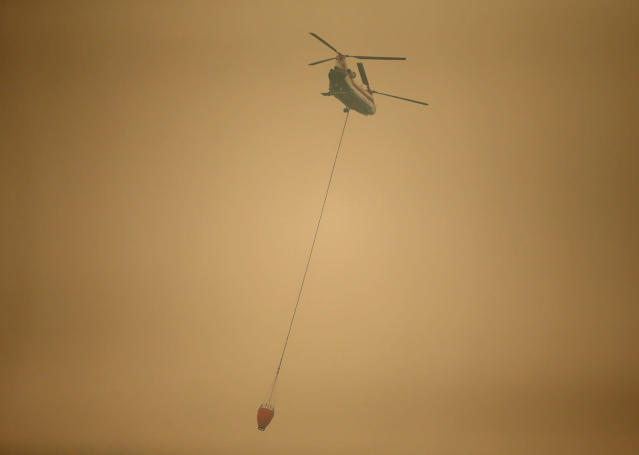 <p>A helicopter with a water bucket flies through dense smoke near Stevenson, Wash., on Sept. 6, 2017, as it works to battle the Eagle Creek wildfire on the Oregon side of the Columbia River Gorge. (Photo: Randy L. Rasmussen/AP) </p>