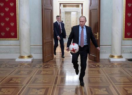 Russian President Vladimir Putin plays with a ball following a meeting with FIFA President Gianni Infantino at the Kremlin in Moscow, Russia November 25, 2016.  Sputnik/Alexei Druzhinin/Kremlin via REUTERS