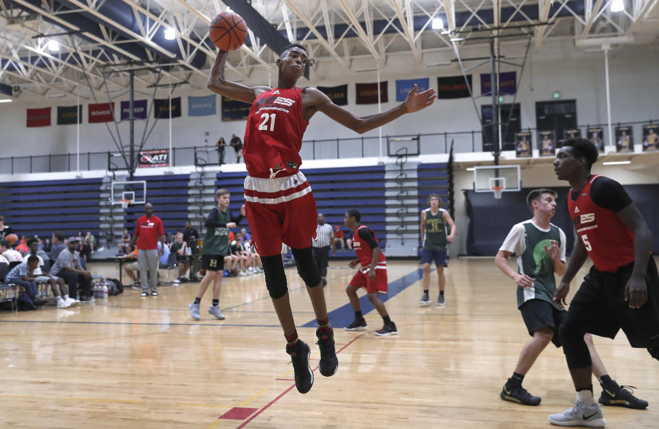 In this Oct. 8, 2017, photo, Emoni Bates pulls down a rebound against Howell High School during a fall league basketball game in Saline, Mich. The 13-year-old, 6-foot-7 basketball player is one of the most coveted young players in hoops. (AP Photo/Paul Sancya)