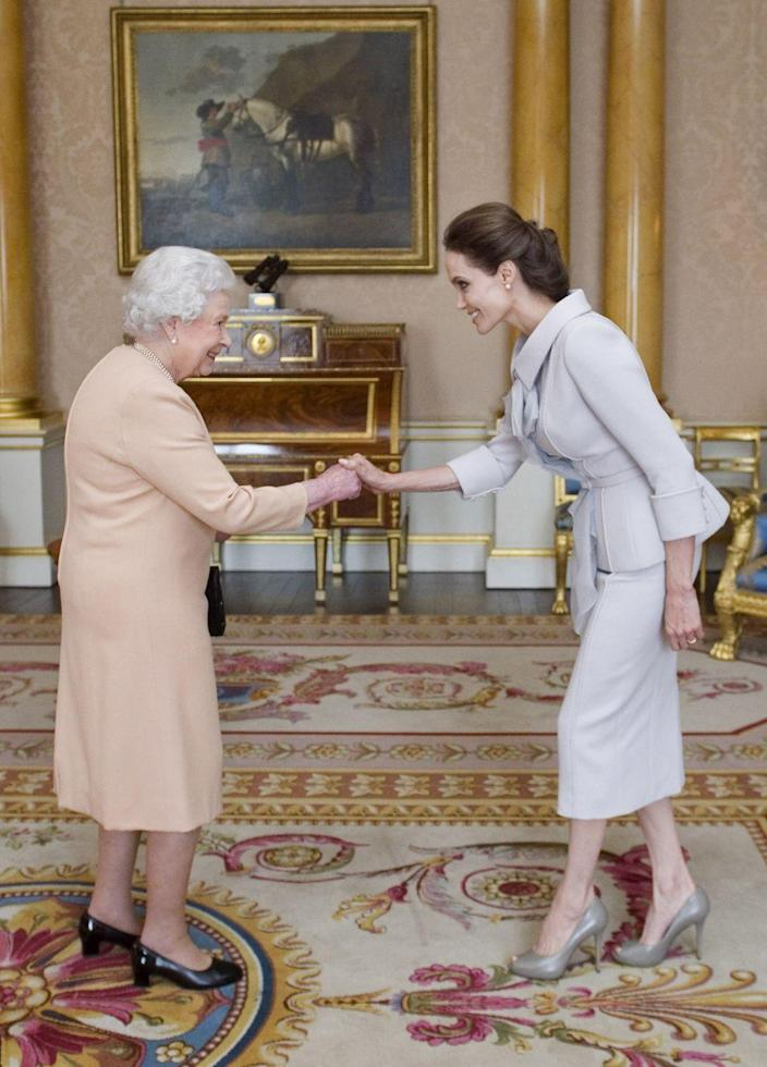 <p> Angelina Jolie wore a pale collared suit to meet the Queen when she received an honorary damehood for her work in UK foreign policies and in the campaign to stop war-zone sexual violence. Can we also get Angie an award for this outfit, though?!</p>