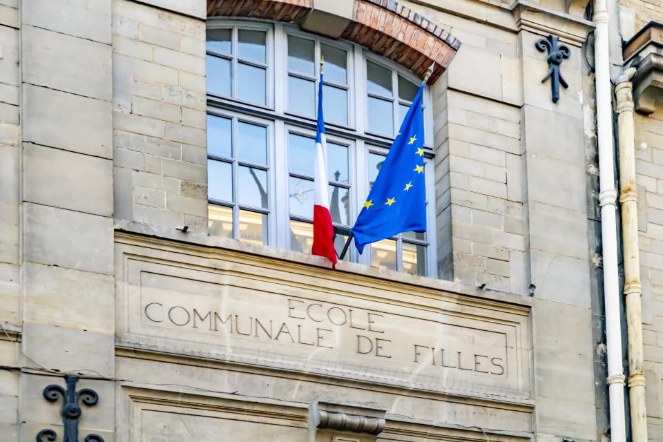 European and French flag hanging on the building exterior of a Girls school in Paris, France.
