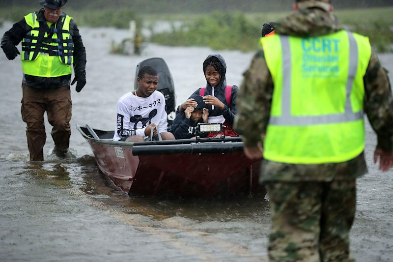 Volunteers from the Civilian Crisis Response Team help rescue three children from their flooded home in James City on Friday.