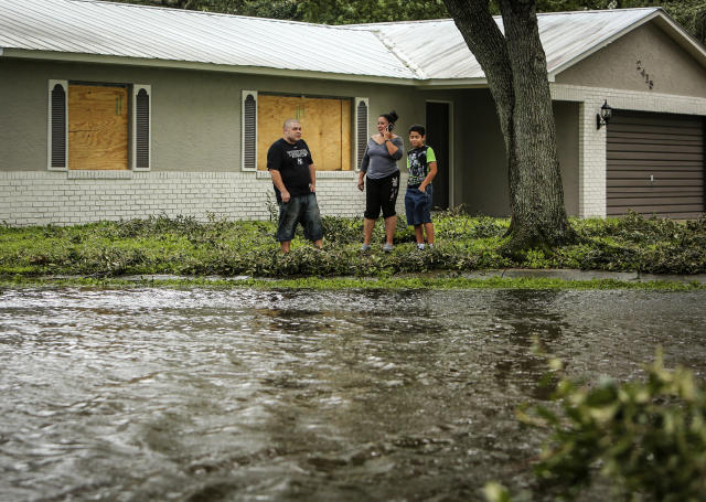 <p><strong>Kissimmee</strong><br>Robert Gonzalez, his wife Maria and son David, 10, survey the flooded Town & Country Drive in front of their home, which is located on Sweetbriar Court where it meets Town & Country in Kissimmee, Fla., on Monday, Sept. 11, 2017. (Photo: Jacob Langston/Orlando Sentinel/TNS via Getty Images) </p>