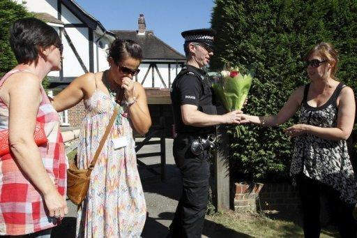 A police officer takes a boquet of flowers from a woman to be added to the growing pile outside a house that is believed to be the British home of a family shot dead in their car in the French Alps