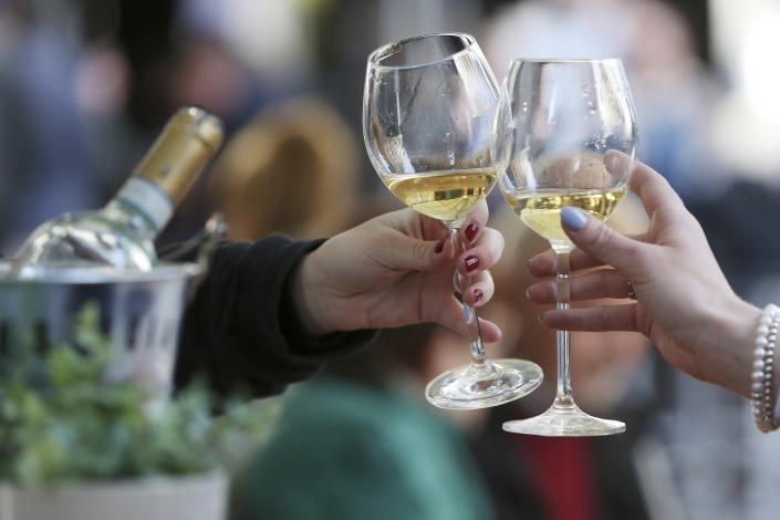 Women toast with white wine at a table in the outdoor area of a restaurant, in Duesseldorf, Germany, Friday, May 21, 2021. After months of forced break, restaurateurs in Duesseldorf are allowed to welcome guests again as of Friday. As in other municipalities in North Rhine-Westphalia, this only applies to the outdoor area and under certain coronavirus measures. (David Young/dpa via AP)