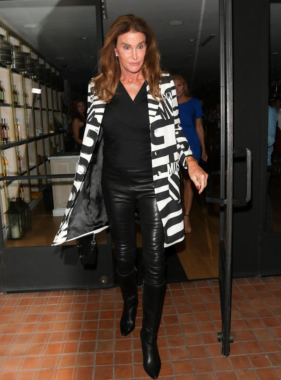 <p>Out to dinner in Los Angeles with friend Candis Cayne, Caitlyn Jenner served up fall style inspiration. Wearing all black — a pair of leather pants, black wrap jersey top, and knee-high boots — she took the monochromatic look to the next level with a Moschino jacket. The black and white bold-lettered coat was certainly a statement piece, and Jenner rightly paired it with a simple outfit.</p>