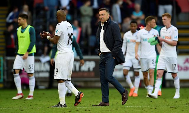 Swansea City's manager, Carlos Carvalhal, follows Federico Fernández (No33) and André Ayew on a lap of dejection after the 2-1 defeat by Stoke.