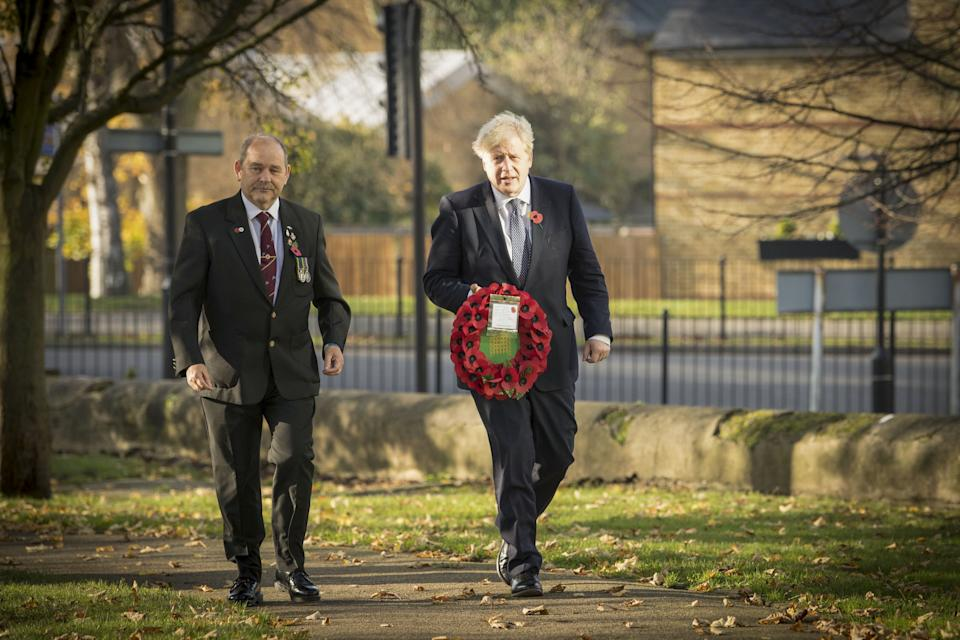 Prime Minister Boris Johnson (right), with Ian Ritchie from Hillingdon and District Royal British Legion, lay a wreath of remembrance at Uxbridge War Memorial in west London, ahead of Remembrance Sunday. (Photo by Stefan Rousseau/PA Images via Getty Images)