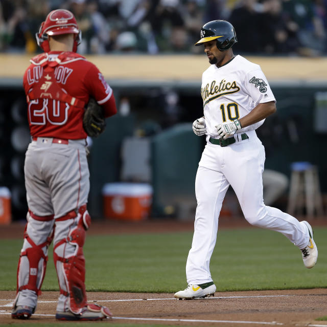 Oakland Athletics' Marcus Semien, right, scores past Los Angeles Angels catcher Jonathan Lucroy (20) after hitting a home run off Angels' pitcher Cam Bedrosian in the first inning of a baseball game Tuesday, May 28, 2019, in Oakland, Calif. (AP Photo/Ben Margot)