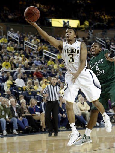 Michigan guard Trey Burke (3) drives past Cleveland State center Devon Long (4) during the first half of their NCAA college basketball game in the second-round of the NIT Season Tip-Off tournament at Crisler Arena in Ann Arbor, Mich., Tuesday, Nov. 13, 2012. (AP Photo/Paul Sancya)
