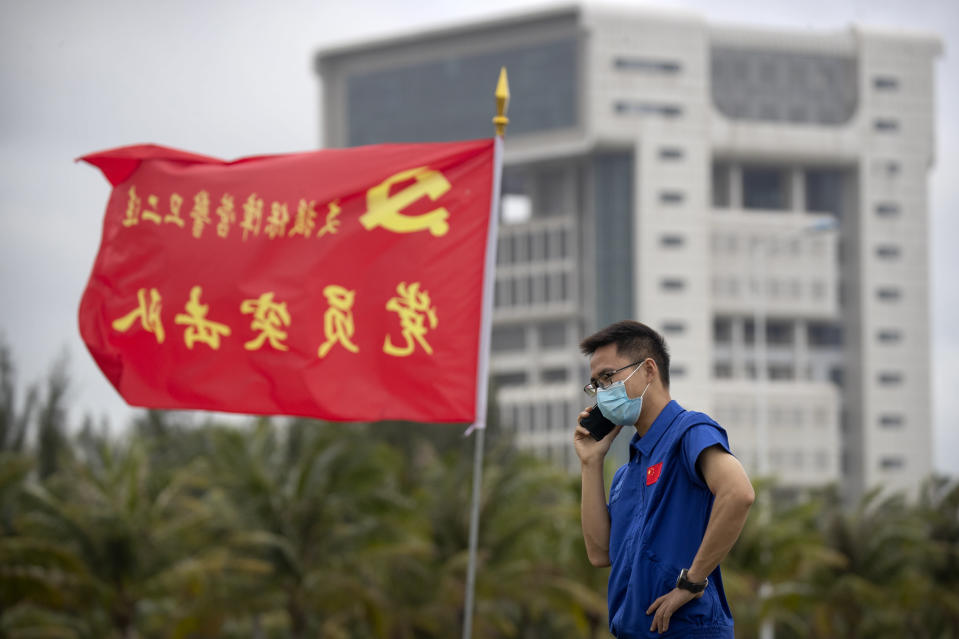 A worker talks on a cellphone near a flag with the logo of the Communist Party of China at the Wenchang Space Launch Site in Wenchang in southern China's Hainan province, Monday, Nov. 23, 2020. Chinese technicians were making final preparations Monday for a mission to bring back material from the moon's surface for the first time in nearly half a century — an undertaking that could boost human understanding of the moon and of the solar system more generally. (AP Photo/Mark Schiefelbein)